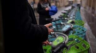 A customer selects a model of Paris' new Velib bicycle-sharing service on 1 January 2018.