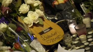Một cây đàn ghi-ta giữa hoa và nến trước cửa nhà hát Bataclan, địa điểm bị tấn công khủng bố ngày 13/11/2015, gần 90 người thiệt mạng tại đây.