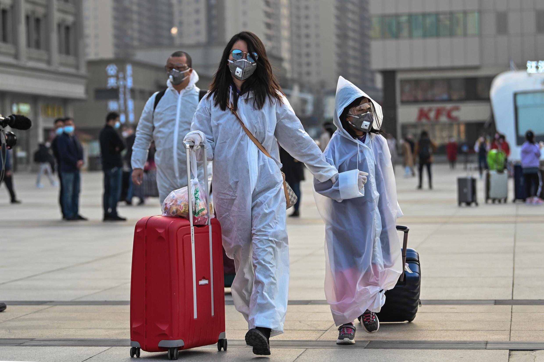 Una mujer y una niña con mascarillas y trajes protectores llegan a la Estación de Tren de Hankou, en Wuhan, para abordar uno de los primeros trenes que saldrán de la ciudad china el 8 de abril de 2020 tras el levantamiento de las restricciones