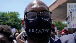 Un manifestant porte un masque sur lequel il a inscrit «I can't breath» - «Je ne peux pas respirer», les mots que prononçait George Floyd lors de son arrestation, juste avant sa mort.