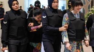 Sur cette photo datée du 24 octobre 2017, on voit l'Indonésienne Siti Aishah (2e à gauche) et la Vietnamienne Doan Thi Huong (d) escortées par des policières pendant la reconstitution de la scène de crime à l'aéroport de Kuala Lumpur.