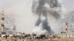 Une colonne de fumée s'élève de la Ghouta, dans la banlieue de Damas, après un probable bombardement aérien de l'aviation syrienne, le 17 mai 2015.