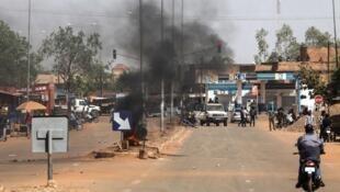 Des manifestants ont enflammé une barricade aux abords de la route qui mène à l'université Ouaga1 où Emmanuel Macron a prononcé un discours devant des étudiants, mardi 28 novembre 2017.