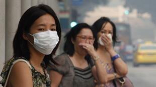Des femmes incommodées par la pollution dans une rue de Singapour, le 20 juin 2013.