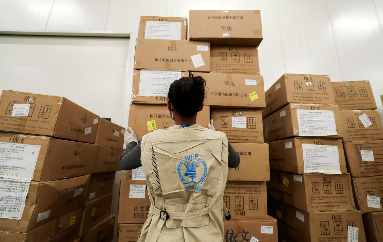 Une employée du PAM organise des colis de secours dans un entrepôt désigné par l'ONU pour l'aide humanitaire à l'Afrique pour lutter contre l'épidémie de Covid-19 à l'aéroport international de Bole à Addis-Abeba, en Éthiopie, le 14 avril 2020.