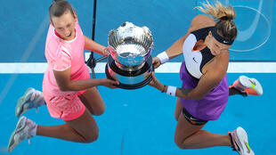 Elise Mertens and Aryna Sabalenka celebrate with the trophy after winning the Australian Open women's doubles final on Friday
