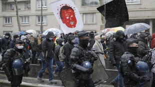 Des agents des forces de l'ordre marchent à côté de manifestants contre le projet de loi sur la sécurité globale, à Paris le 16 janvier 2021.