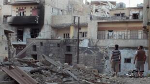 Homens caminham entre ruínas do bairro de Bab Tobmor em Homs, na quinta-feira (12). O governo brasileiro condenou a violência contra civís na Síria.