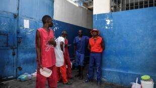 Des détenus d'un centre pénitenticier de Port-au-Prince attendent leur ration de nourriture, en août 2019.