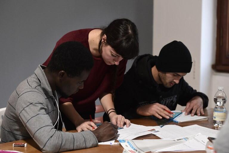 Une bénévole aide des migrants à étudier pendant un cours dans le cadre d'un programme d'aide à l'intégration des migrants, en Italie.