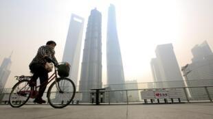 Une jeune femme en vélo à Shanghaï. Photo datée du 12 février 2015.