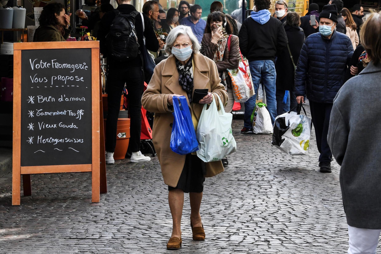 Una mujer con una mascarilla camina por la calle Mouffetard, el 2 de mayo de 2020, en París.