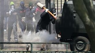 Manifestantes chilenos atacam um tanque da polícia durante protesto em Santiago.