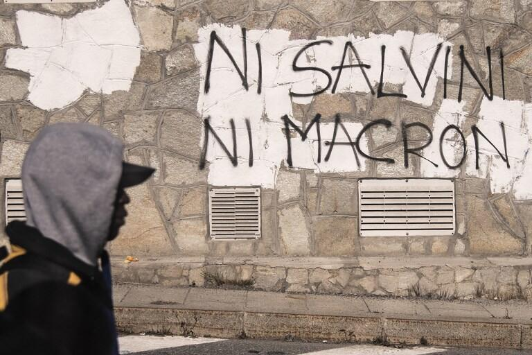 """A migrant walks past an inscription reading, in French, """"Neither Salvini, nor Macron"""" on October 21, 2018 in the Alpine border town of Claviere, some 100 kilometers west of Turin."""