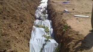 Enterro de vítimas do conflito sírio encontradas em Daraya, próxima da capital Damasco, no domingo.