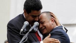 """O vice Nicolas Maduro (esq.), designado herdeiro político pelo próprio Chávez, abraça seu """"rival"""" potencial Diosdado Cabello após votação na Assembleia Nacional.."""