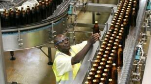 Funcionário faz inspeção de garrafas de cerveja em uma fábrica em Nairobi, Quênia.