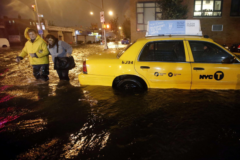 Pedestres caminham em meio a água enquanto um táxi está submerso no Brooklyn.