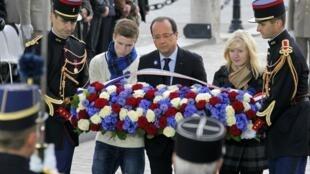 Ao lado dos filhos de um militar morto no Afeganistão, o presidente François Hollande deposita flores em homenagem aos soldados mortos pela França, no Arco do Triunfo, em Paris.