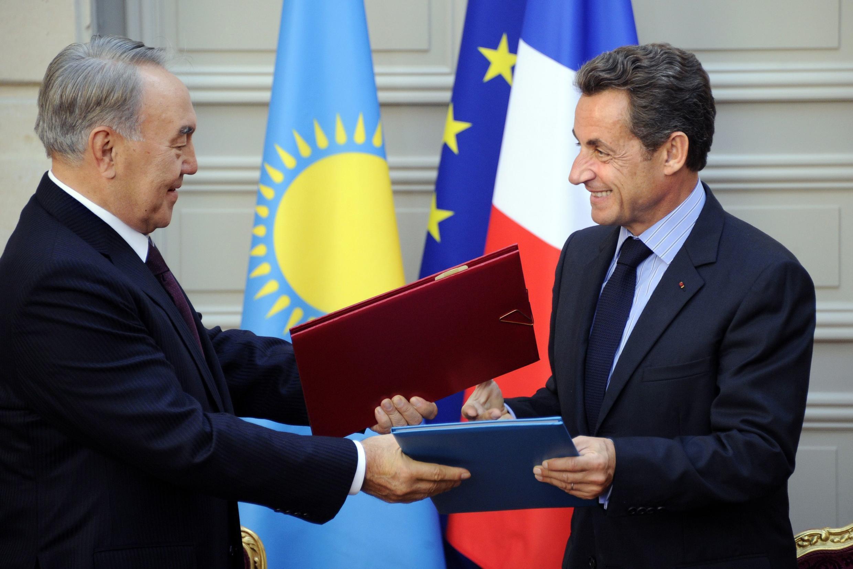 Нурсултан Назарбаев и Николя Саркози обмениваются экземплярами подписанных соглашений в Париже (архив)