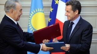 Нурсултан Назарбаев и Николя Саркози обмениваются экземплярами подписанных соглашений