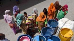 Les femmes attendent près d'un camion-citerne pour avoir de l'eau, le 19 juin 2018 à New Delhi, en Inde.