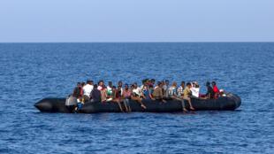 Des migrants attendent d'être pris en charge par les garde-côtes italiens, à 30 milles marins de la côte libyenne, le 6 août 2017.