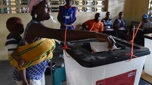 A woman casts her ballot at a polling station in Monrovia for elections on 10 October.